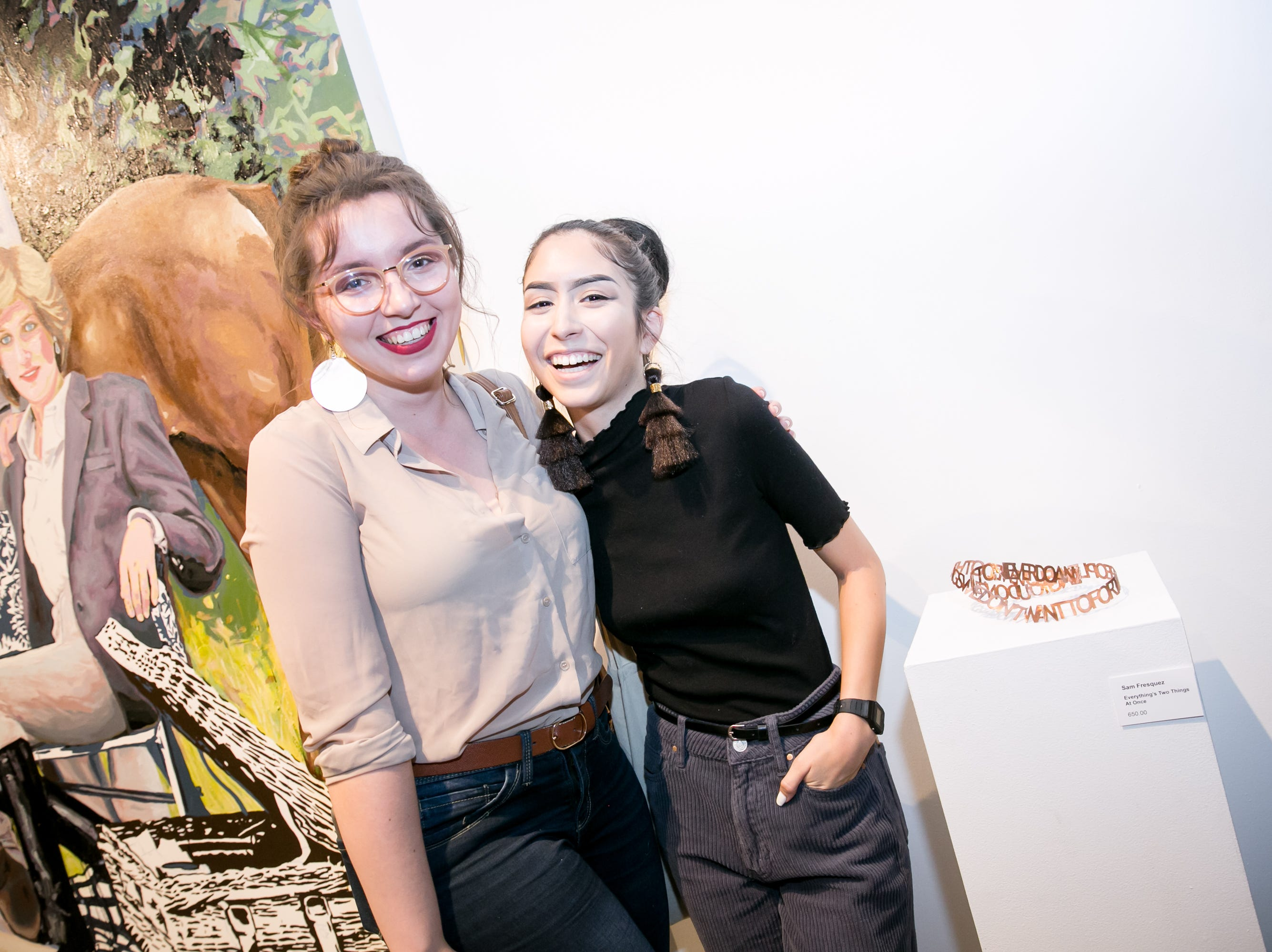 Sam Fresquez (right) poses with a friend next to her art at Chaos Theory 19 at Legend City Studios during First Friday on October 5, 2018.