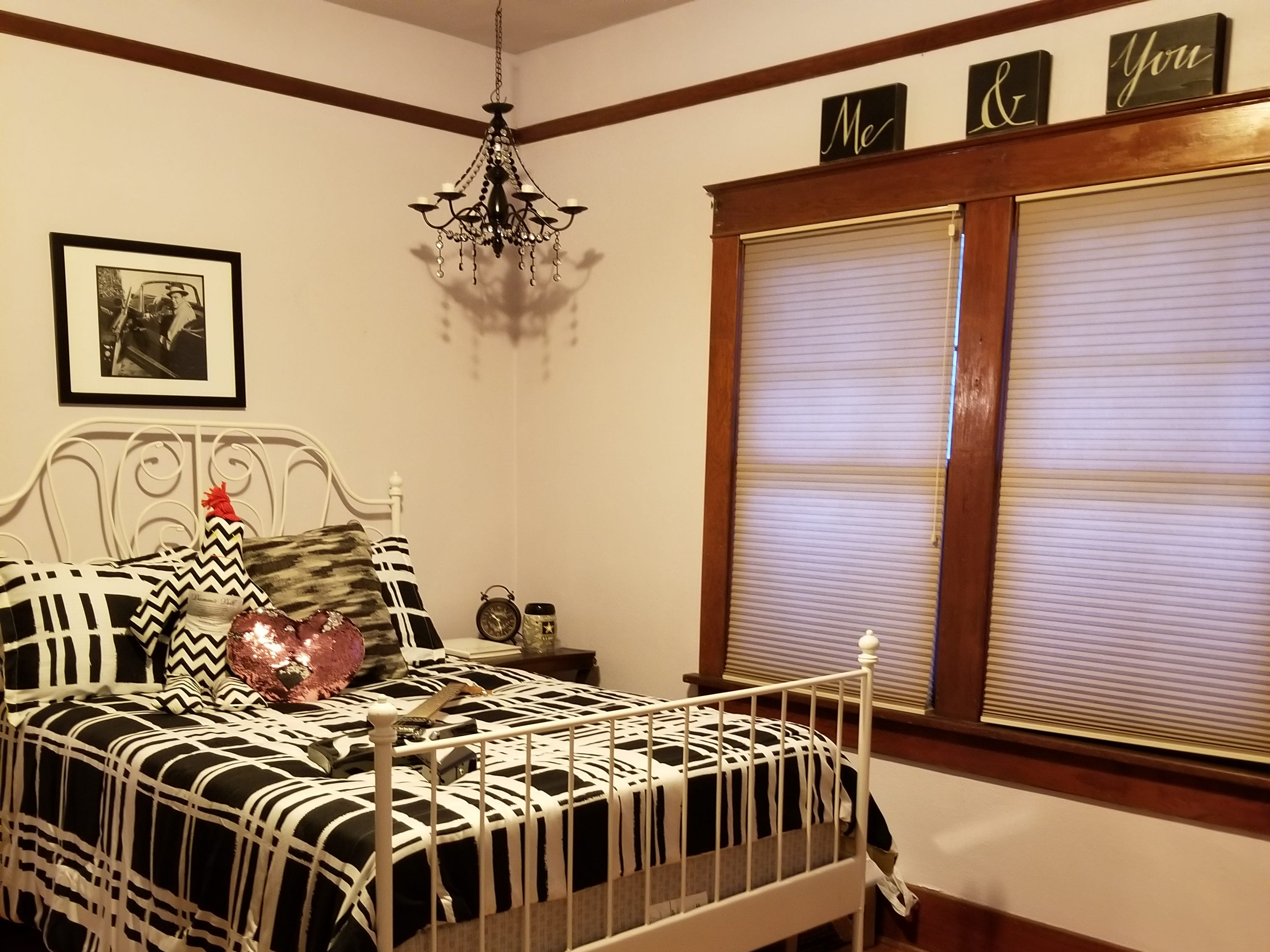 An antique iron bed sets the theme for this fun room design, featuring the original yet restored hardwoods, and movie-themed decorations.