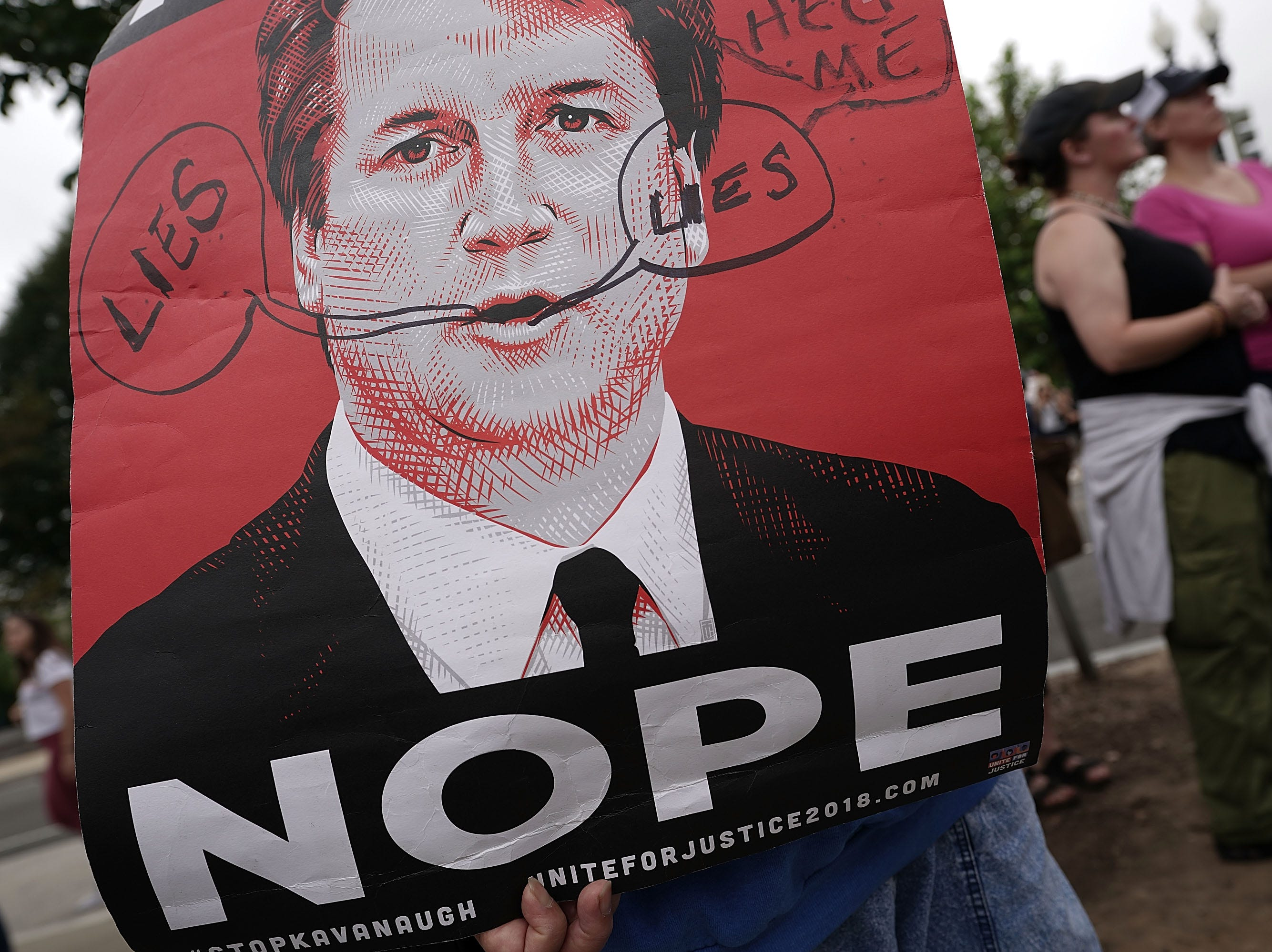 "WASHINGTON, DC - OCTOBER 06:  A demonstrator holds up a ""NOPE"" poster during a protest against the confirmation of Supreme Court nominee Judge Brett Kavanaugh, outside of the Supreme Court, October 6, 2018 in Washington, DC. The Senate is set to hold a final vote Saturday evening to confirm the nomination of Judge Brett Kavanaugh to the U.S. Supreme Court. (Photo by Alex Wong/Getty Images)"