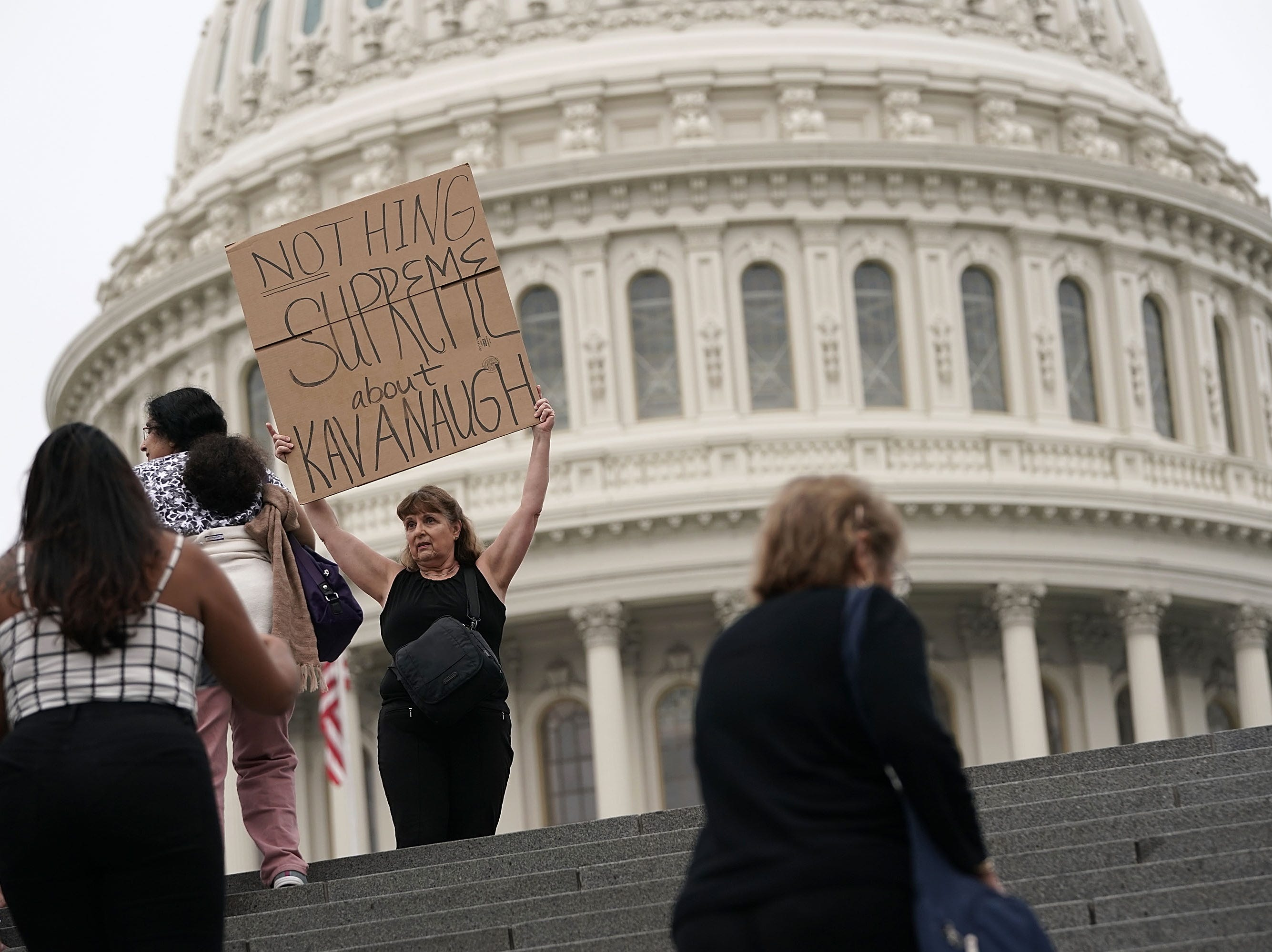 WASHINGTON, DC - OCTOBER 06:  A demonstrator holds up a sign during a protest against the confirmation of Supreme Court nominee Judge Brett Kavanaugh, outside of the Supreme Court, October 6, 2018 in Washington, DC. The Senate is set to hold a final vote Saturday evening to confirm the nomination of Judge Brett Kavanaugh to the U.S. Supreme Court. (Photo by Alex Wong/Getty Images)