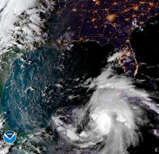 Esta imagen satelital proporcionada por la Administración Nacional Oceánica y Atmosférica muestra una vista de la tormenta tropical Michael, abajo a la derecha, agitándose mientras se dirige hacia el Panhandle de Florida, el domingo 7 de octubre de 2018, a las 6:52 p.m. Hora del este.