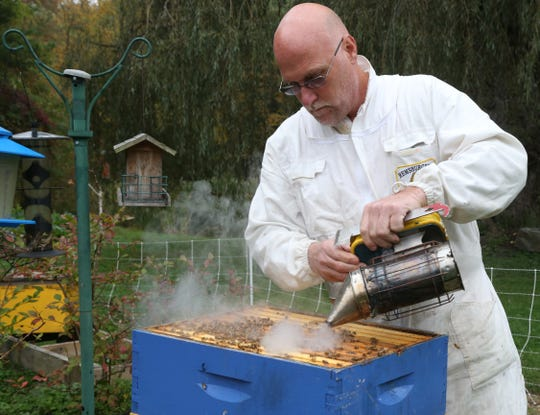 Dennis Remsburger smokes a beehive at his home in Pleasant Valley on October 8, 2018. Pumping smoke into a beehive calms the bees and makes them easier to work with.