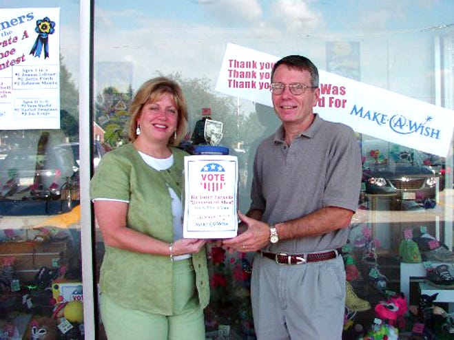 Bob Reineberg presents a check for $916 to Ann Waltman of the Make-A-Wish Foundation in September 2005. The money was raised through Reineberg's Decorate a Shoe Contest. Local children decorated 108 shoes. Customers voted for their favorite shoes by donating 25 cents per vote. Winners in the 4 to 8 age group are Jemma Lehner, first; Jerin Firth, second; and Rebecca Shorts, third. Winners in the 9 to 13 age group are Amanda Wivell, first; Josiah Bigelow, second; and Kayla Groft, third. Winners in the 14 to 18 age group are Sara Warfel, first; Rachel Douglass, second; and Jon Krape, third.
