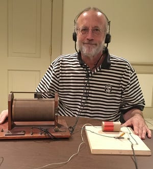 "Dennis Kunkle is shown with a typical crystal radio receiver he purchased (at left) and a ""foxhole radio"" he built (at right)."