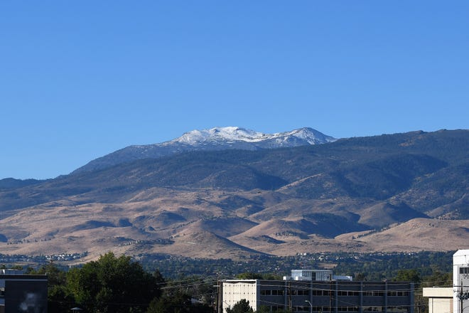 A dusting of on Mt. Rose snow visible over the rooftops of buildings near downtown Reno on Oct. 8, 2018.