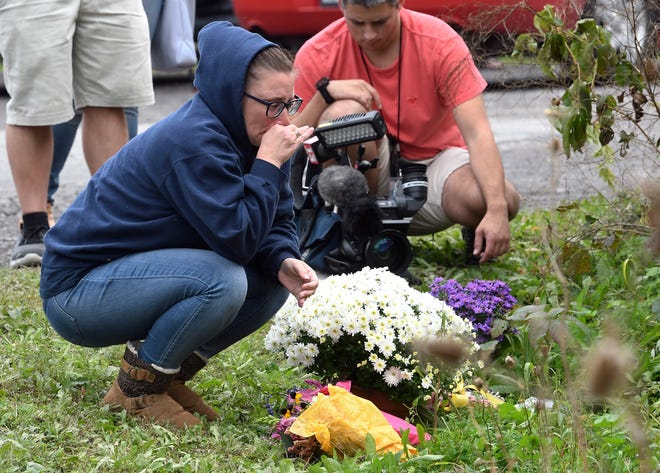 A woman kneels after placing flowers, Sunday, Oct. 7, 2018, at the scene where 20 people died as the result of a limousine crashing into a parked and unoccupied SUV at an intersection a day earlier, in Schoharie, N.Y.
