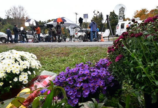 Television networks broadcast at the roadside memorial scene of Saturday's fatal limousine crash in Schoharie, N.Y., Monday, Oct. 8, 2018. A limousine loaded with people headed to a birthday party blew a stop sign at the end of a highway and slammed into an SUV parked outside a store, killing all people in the limo and a few pedestrians, officials and relatives of the victims said.