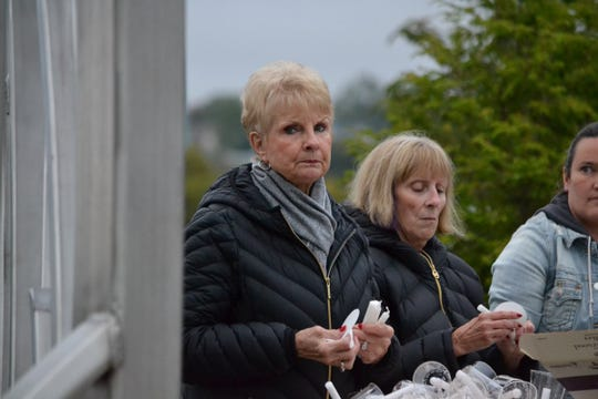 Amsterdam residents slowly gather at Mohawk Valley Gateway Overlook Pedestrian Bridge for a candlelight vigil for victims of the limo crash in Schoharie Monday night.