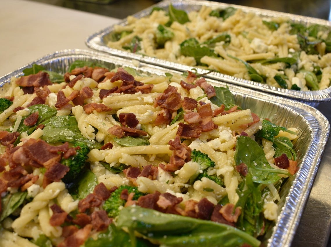 A cheesy pasta with broccoli and greens ready for the oven at Red Bicycle Catering.