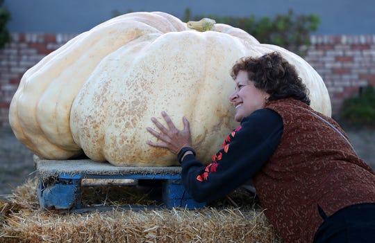 Carolyn Gordon hugs a pumpkin before the 45th annual Safeway World Championship Pumpkin Weigh-Off on Monday, Oct. 8, 2018, in Half Moon Bay, Calif.