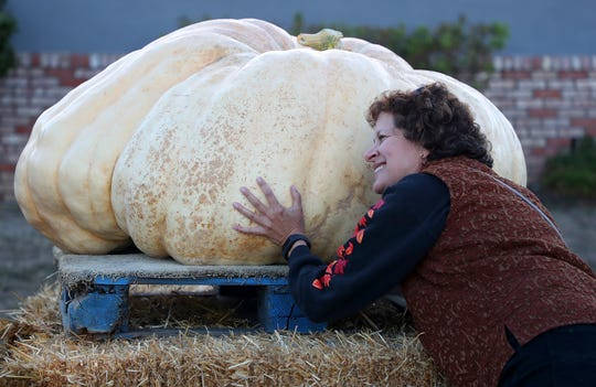 Carolyn Gordon hugs a pumpkin before the 45th annual Safeway World Championship Pumpkin Weigh-Off on Monday, Oct. 8, 2018, in Half Moon Bay, Calif.