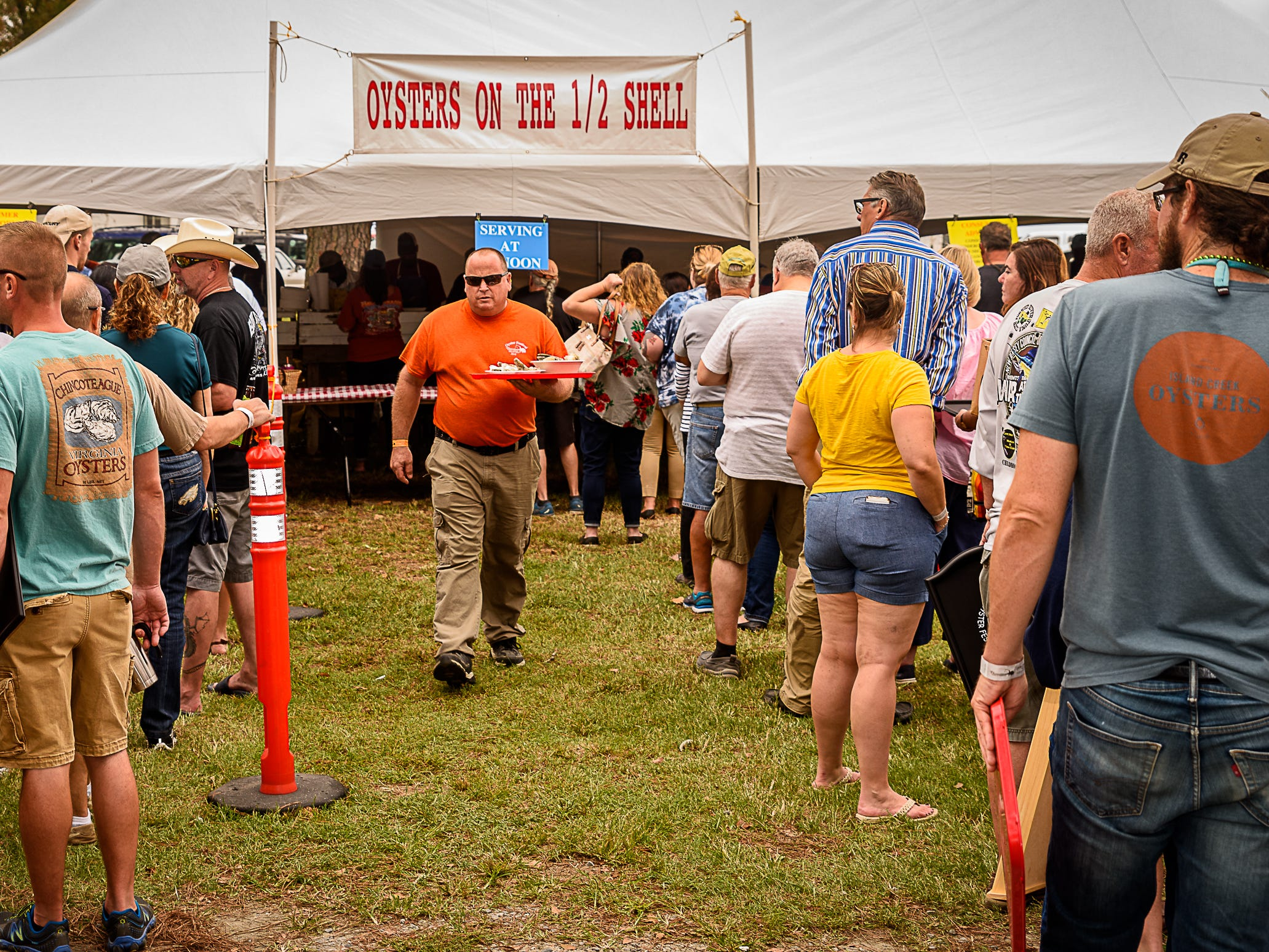 A man leaves with his plate of oysters as others wait patiently in line at Chincoteague Oyster Festival.