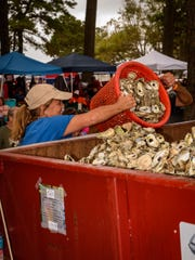 Volunteers from the Nature Conservancy oyster shells into a bin for re-seeding oyster beds.