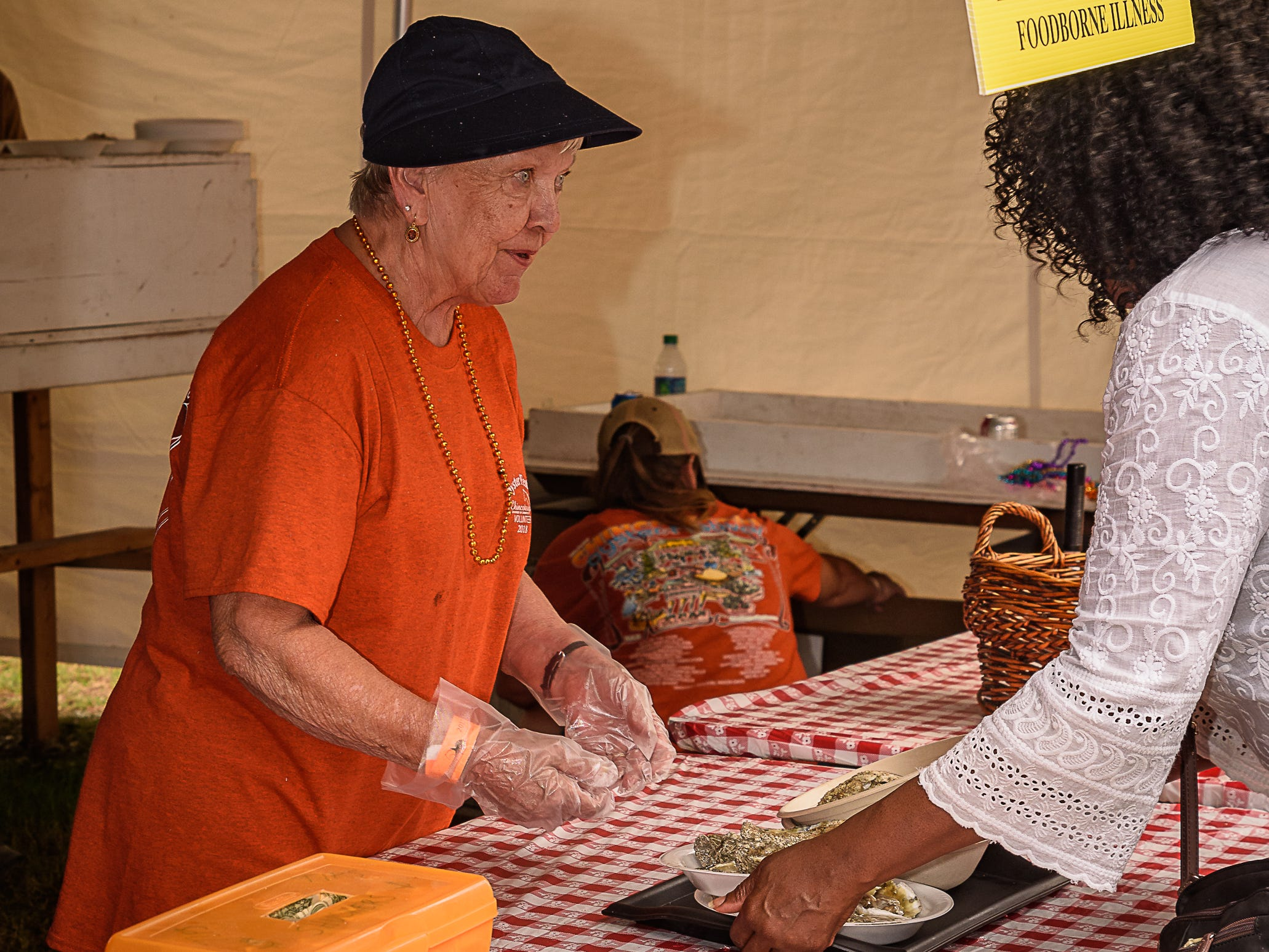 A volunteer hands out steamed oysters at the Chincoteague Oyster Festival.