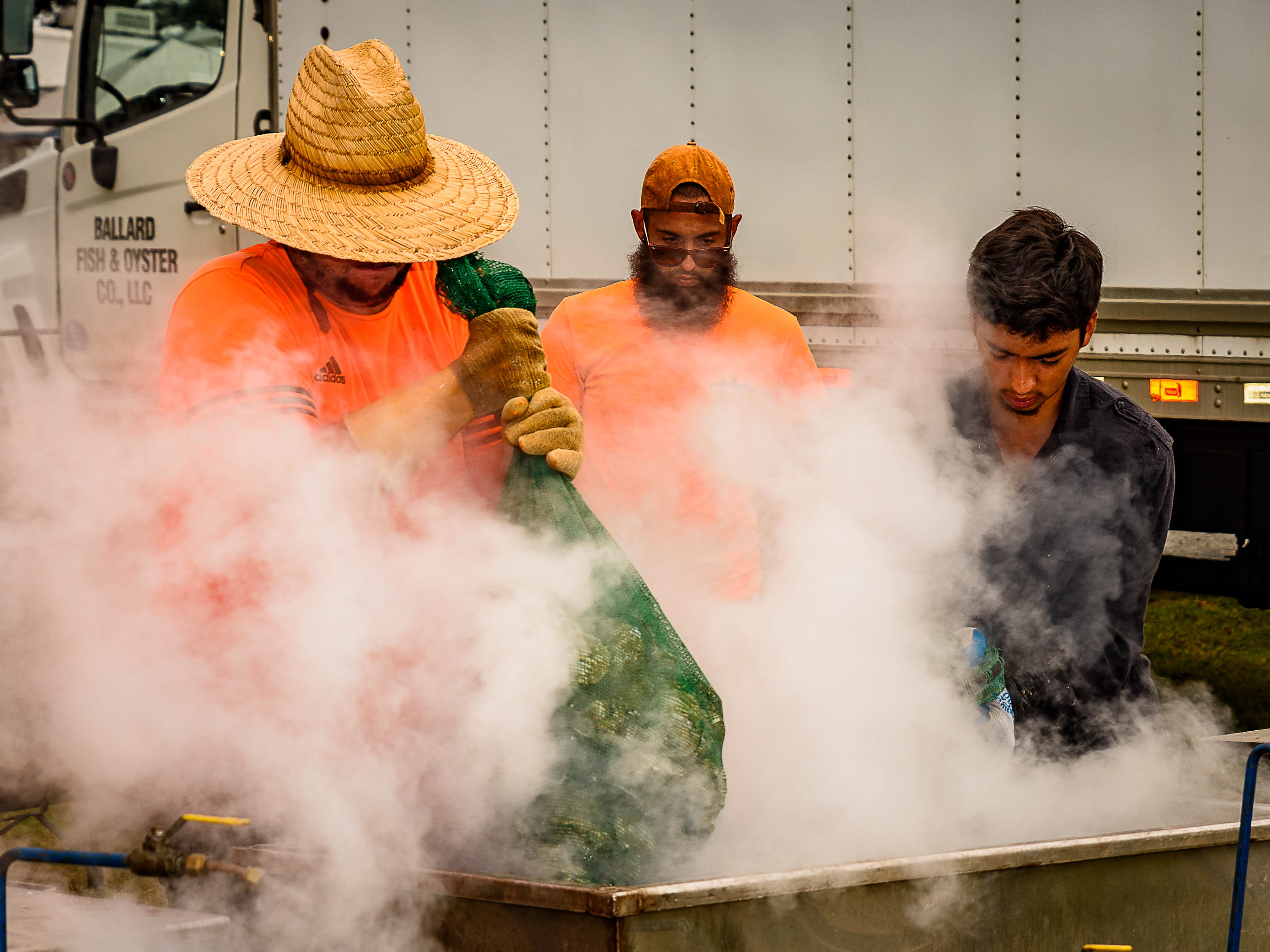 Clouds of steam escape the vats being used to steam oysters at the festival.