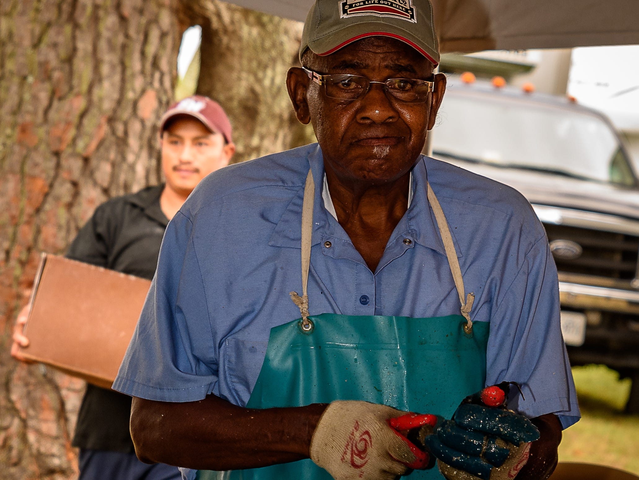 One of several shuckers  is busy at the Oyster Festival on Saturday.