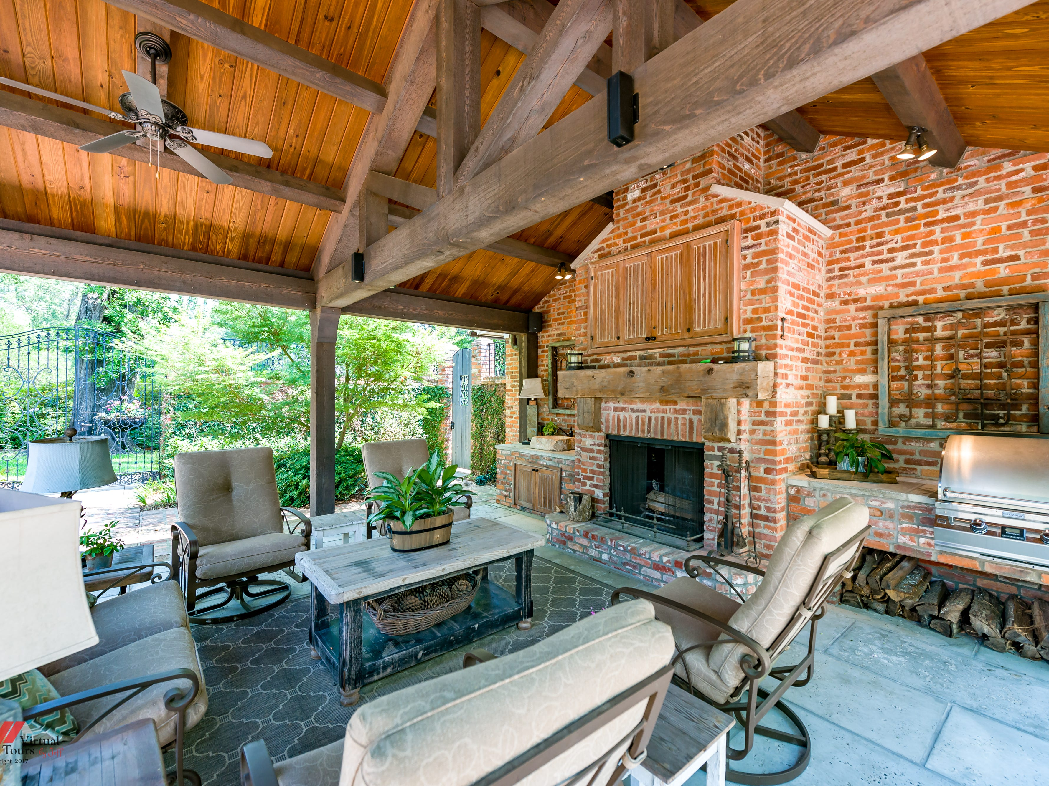 The outdoor kitchen features a cathedral ceiling and wood burning fireplace.