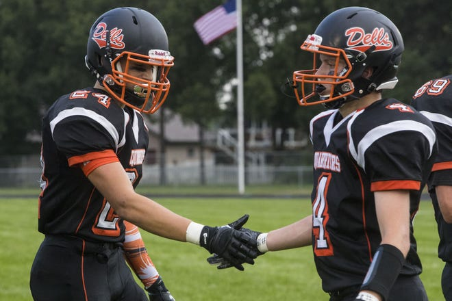 Dell Rapids Coby Maeschen (24) shakes hands with his teammate Tate Kolbeck (4) before the game against Dakota Valley on Friday, Aug. 24, 2018 at Dell Rapids High School.