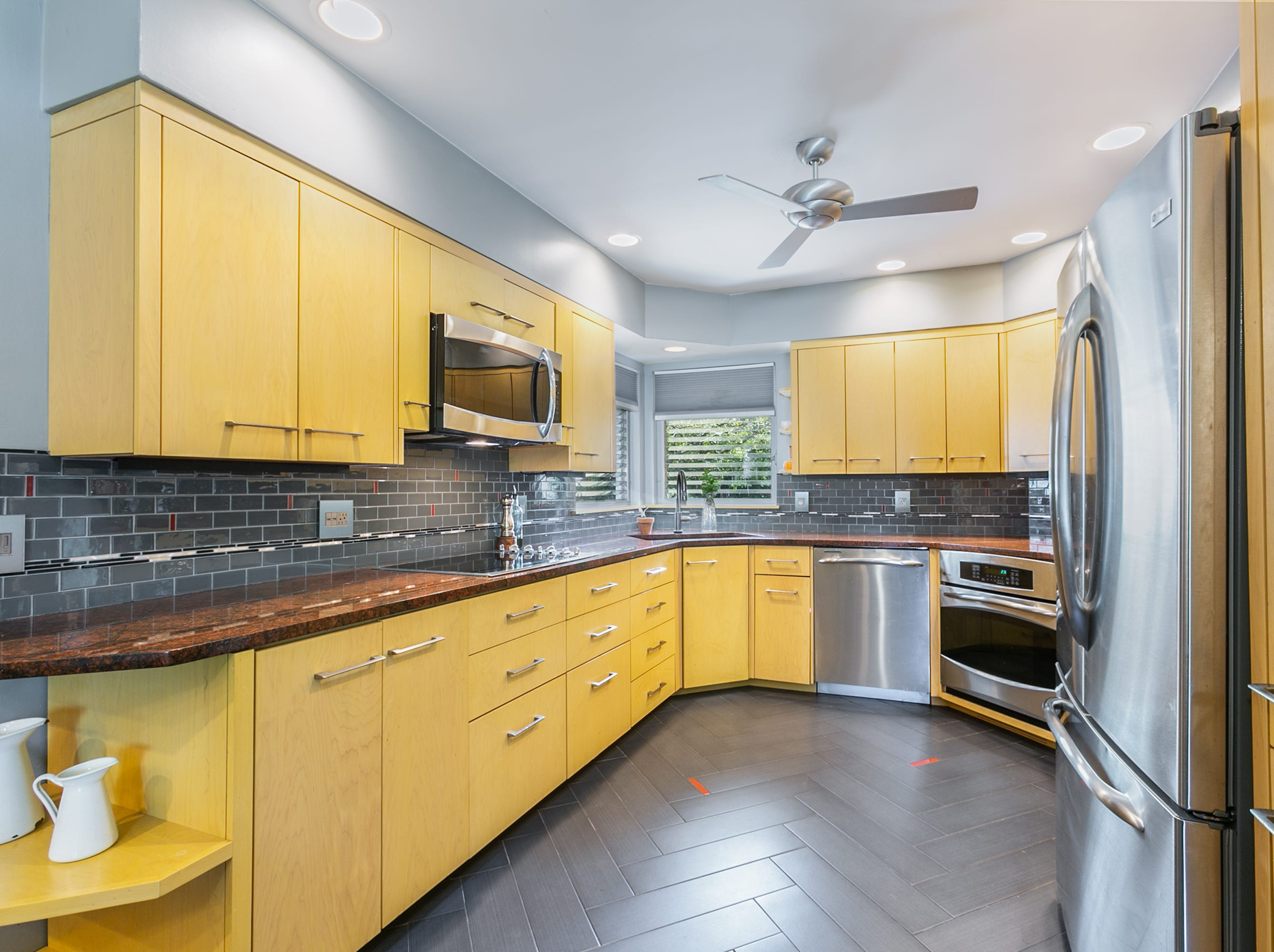 Keri and Aaron updated the kitchen with a new floor, backsplash, granite counter and appliances, but kept the charm of the yellow maple cabinets and corner window.