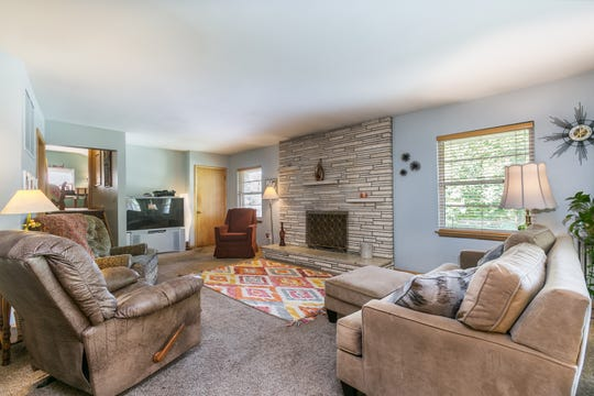The family room offers a somewhat cozier space to hang out as a family. It is anchored by a roman brick fireplace with floating shelves.