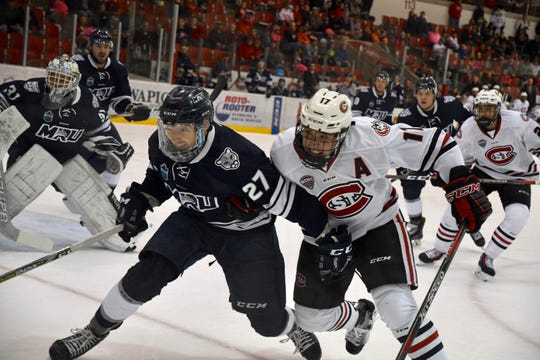 St. Cloud State's Jacob Benson (right) and Mount Royal University's Grant Baker (27) battle for the puck Sunday at the Herb Brooks National Hockey Center. Benson had a power-play goal in the Huskies' 6-2 exhibition win.