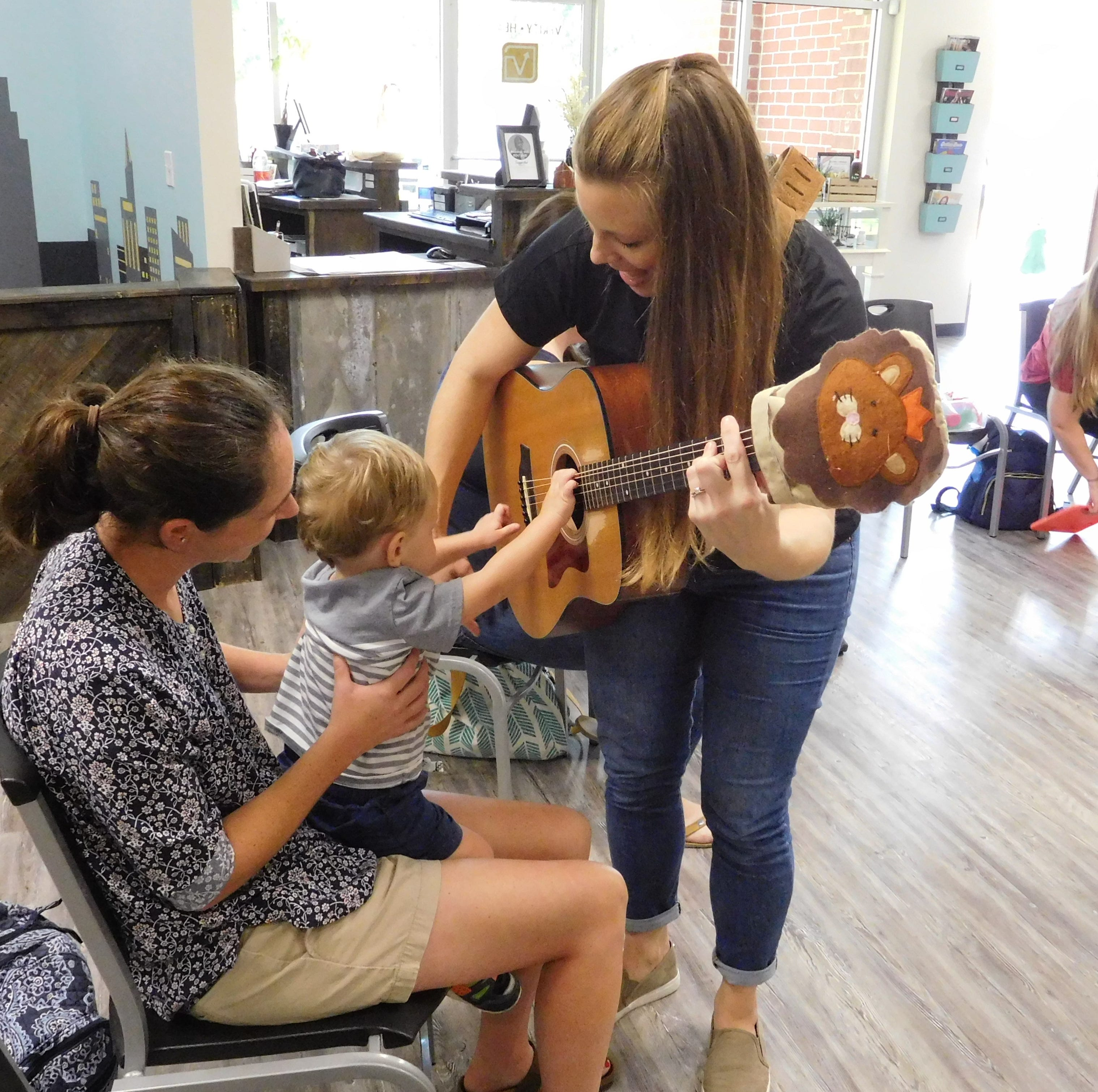 Abby Peters and her son Luke get to strum Michelle Pellito's guitar.
