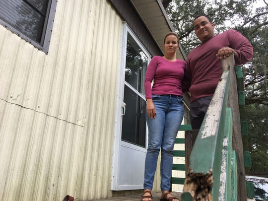 Katia Montalvo, 30, and her husband Jose Martinez, 32, stand in front of their mobile home in the Greenwood Trailer Park off Old St. Augustine Road Monday, Oct. 8, 2018.