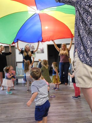 Children sing and dance under the rainbow parachute at Little Ditties early learning music class.