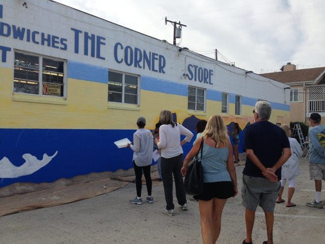 STAR FILE PHOTO: Onlookers watch a mural being painted on The Corner Store in Silver Strand in 2018.