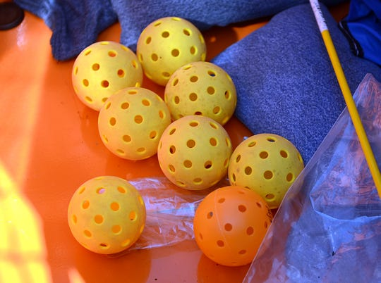 File: Large perforated polymer balls, similar to a wiffle ball, are used to play pickleball.