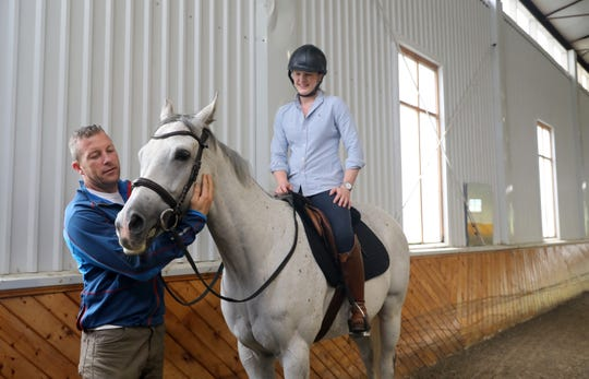 James McKenna greets Nola after Caroline Goodman-Thomases went for a ride in the arena at their farm in Clinton Corners Oct. 2, 2018. The couple is transforming the historic farm that sat abandoned for many years, completely overgrown and falling apart. They have have been painstakingly restoring the horse farm to it's original beauty and are opening it up as Thomases Equestrian for lessons, training and boarding.