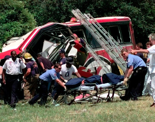 Emergency workers remove the body of one of the victims of a bus crash May 9, 1999, in New Orleans, where a chartered bus carrying members of a casino club on a Mother's Day gambling excursion ran off a highway, killing 22 people.