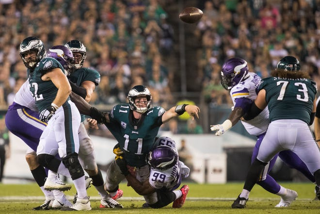 Eagles' Carson Wentz (11) gets rid of the ball while being brought down in the backfield Sunday at Lincoln Financial Field.