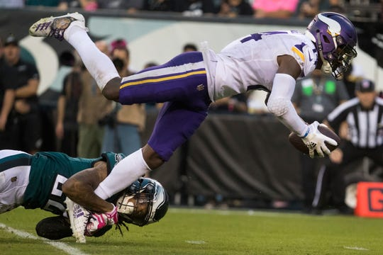 Minnesota's Stefon Diggs (14) is brought down by Philadelphia's Sidney Jones (22) Sunday at Lincoln Financial Field.