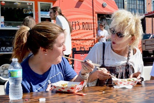 In this file photo, diners enjoy sushi at the Falls Town Food Truck Challenge & Festival, between 9th to 10th Streets on Ohio St.