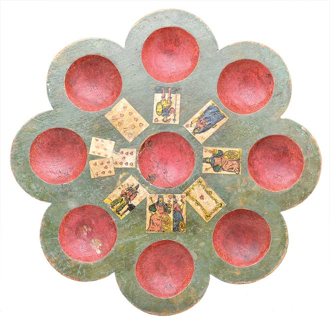 This Pope Joan game board is carved from wood and painted. It sold for $1,007 at a James D. Julia auction in Maine. It is made from a cut-out wooden circle and is 12 1/2 inches in diameter.