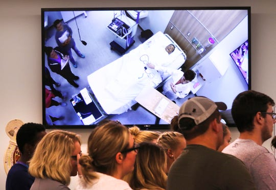 Students watch as Ohio University Zanesville nursing coordinator Carol Schaumleffel explains a procedure in the school's new nursing lab. Large screens dot the room to help students see demonstrations.