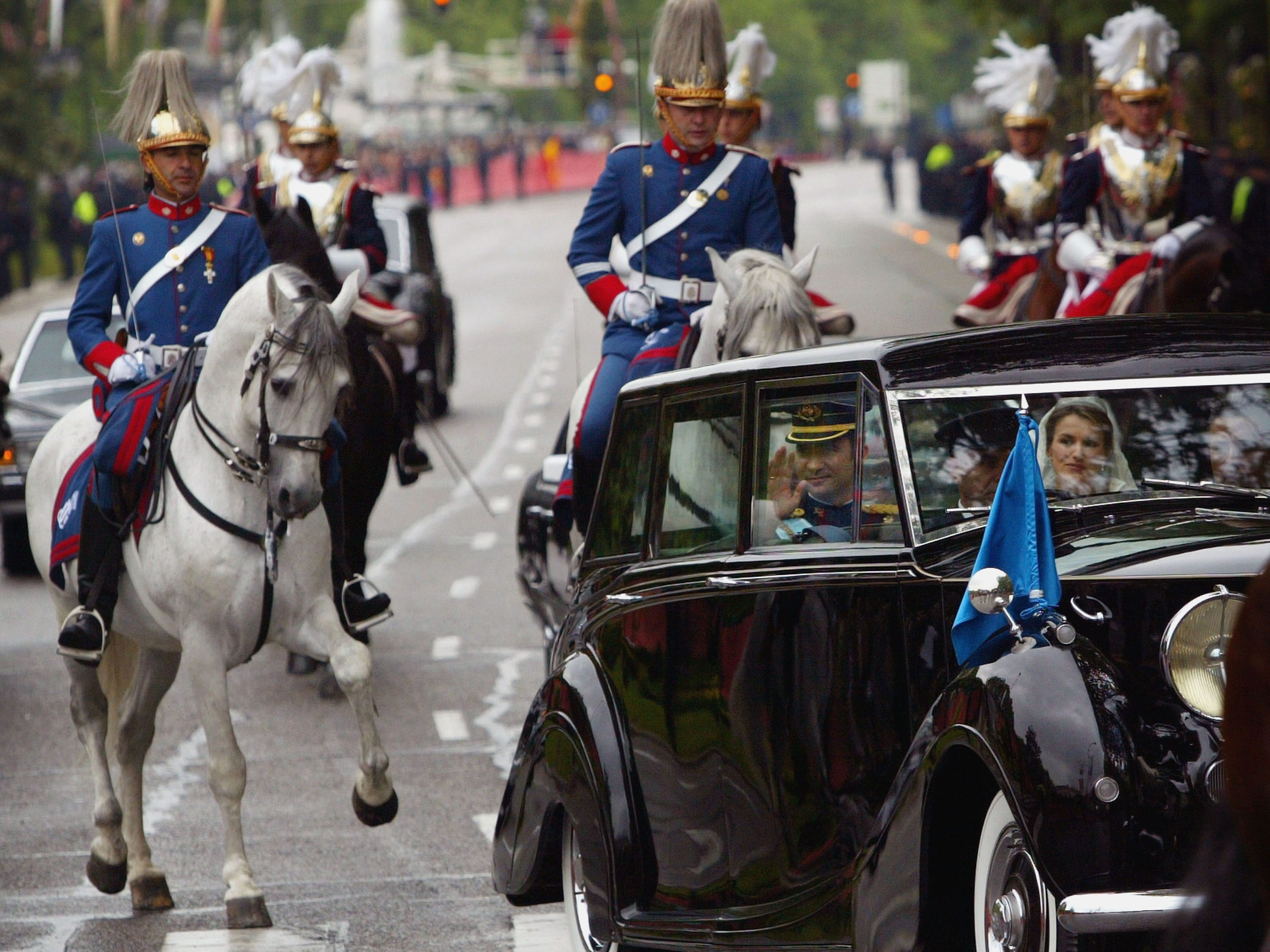 Spain's Crown Prince Felipe de Bourbon and his bride Letizia Ortiz wave from their limousine after their wedding ceremony May 22, 2004 in Madrid.
