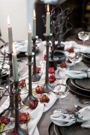Silver or black candles provide spooky lighting for a Halloween party.