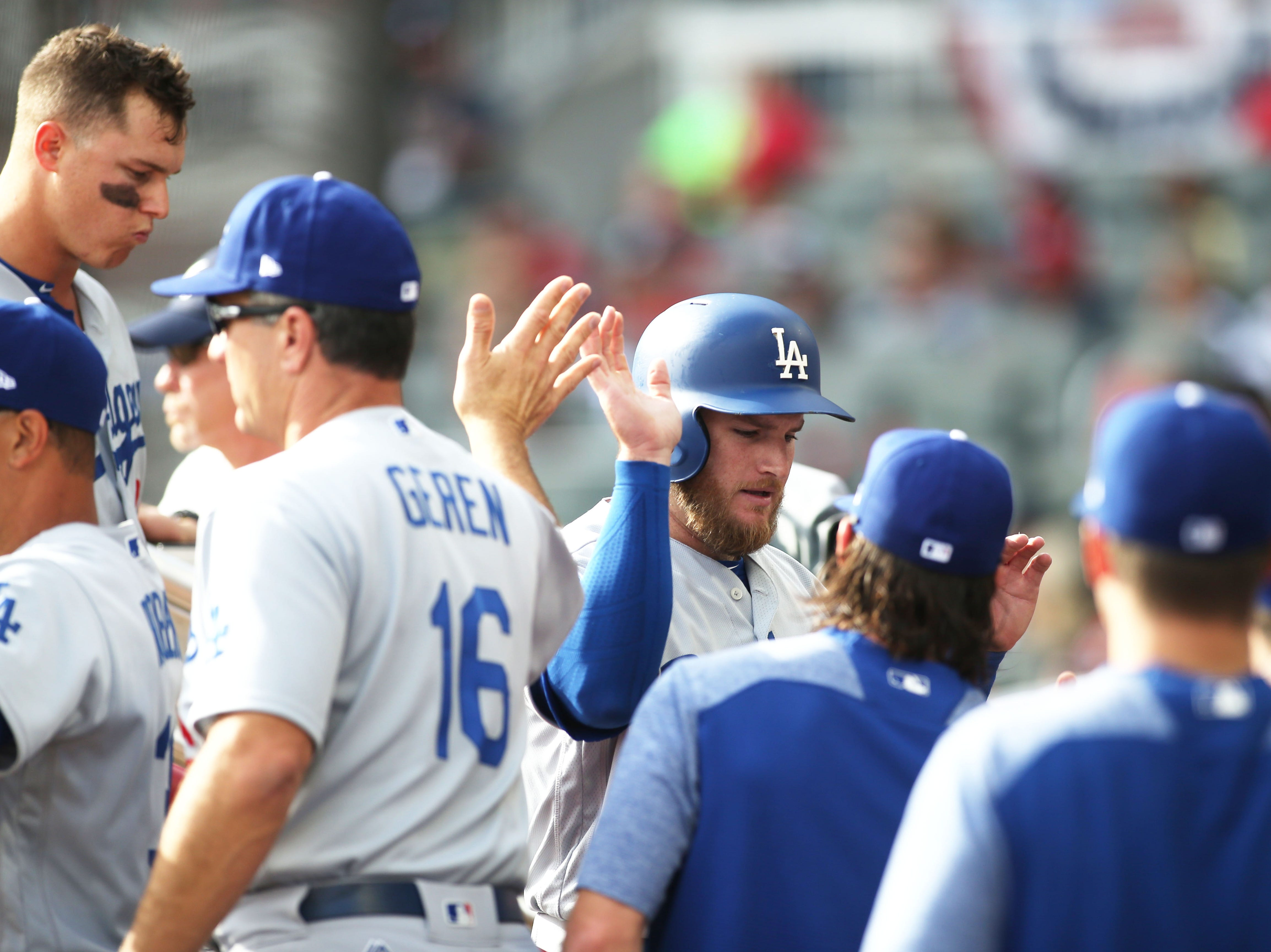 NLDS Game 4: Dodgers first baseman Max Muncy high-fives teammates after scoring a run in the first.
