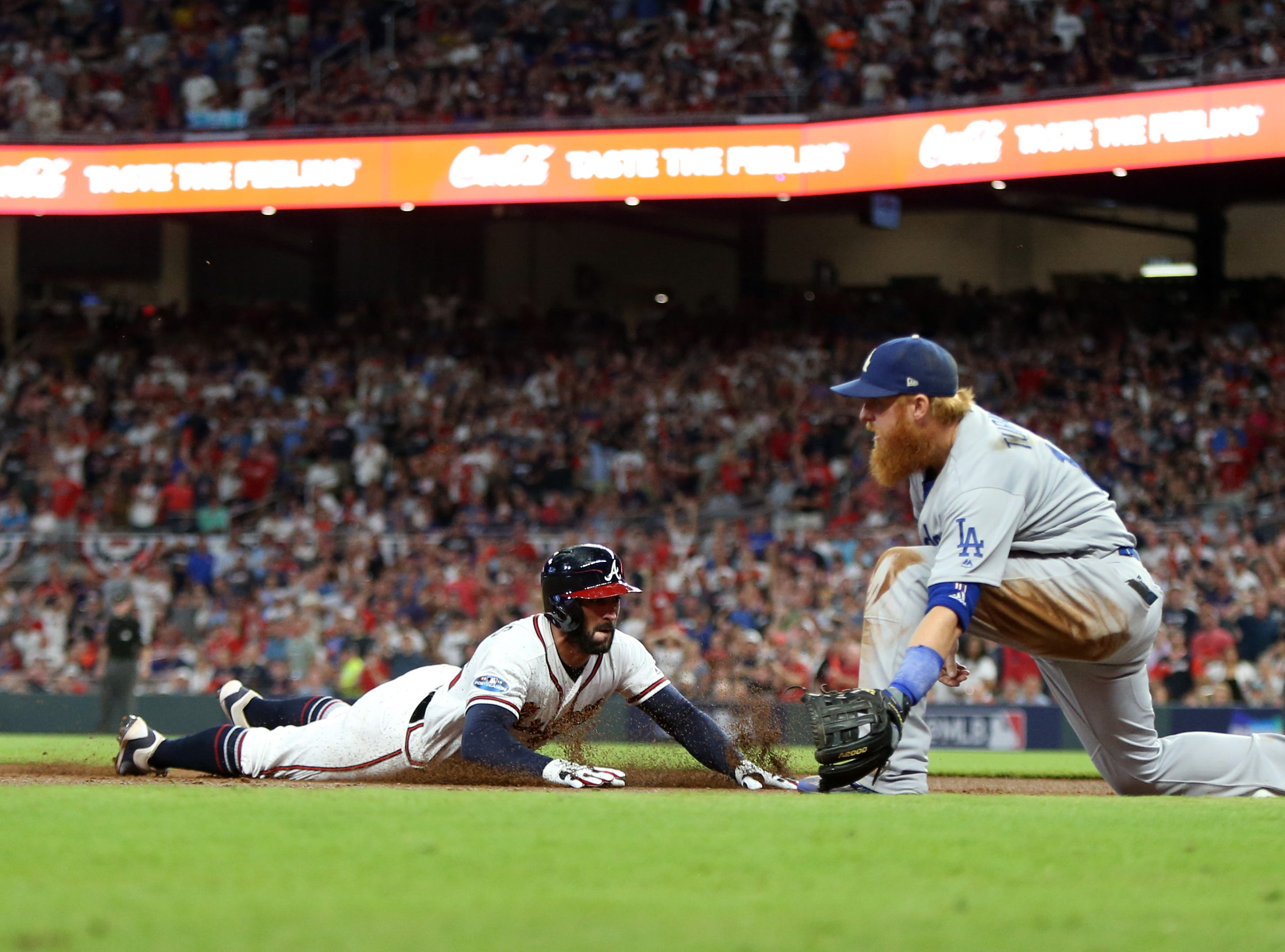 NLDS Game 3: Atlanta's Nick Markakis slides safely into third base in the second inning.