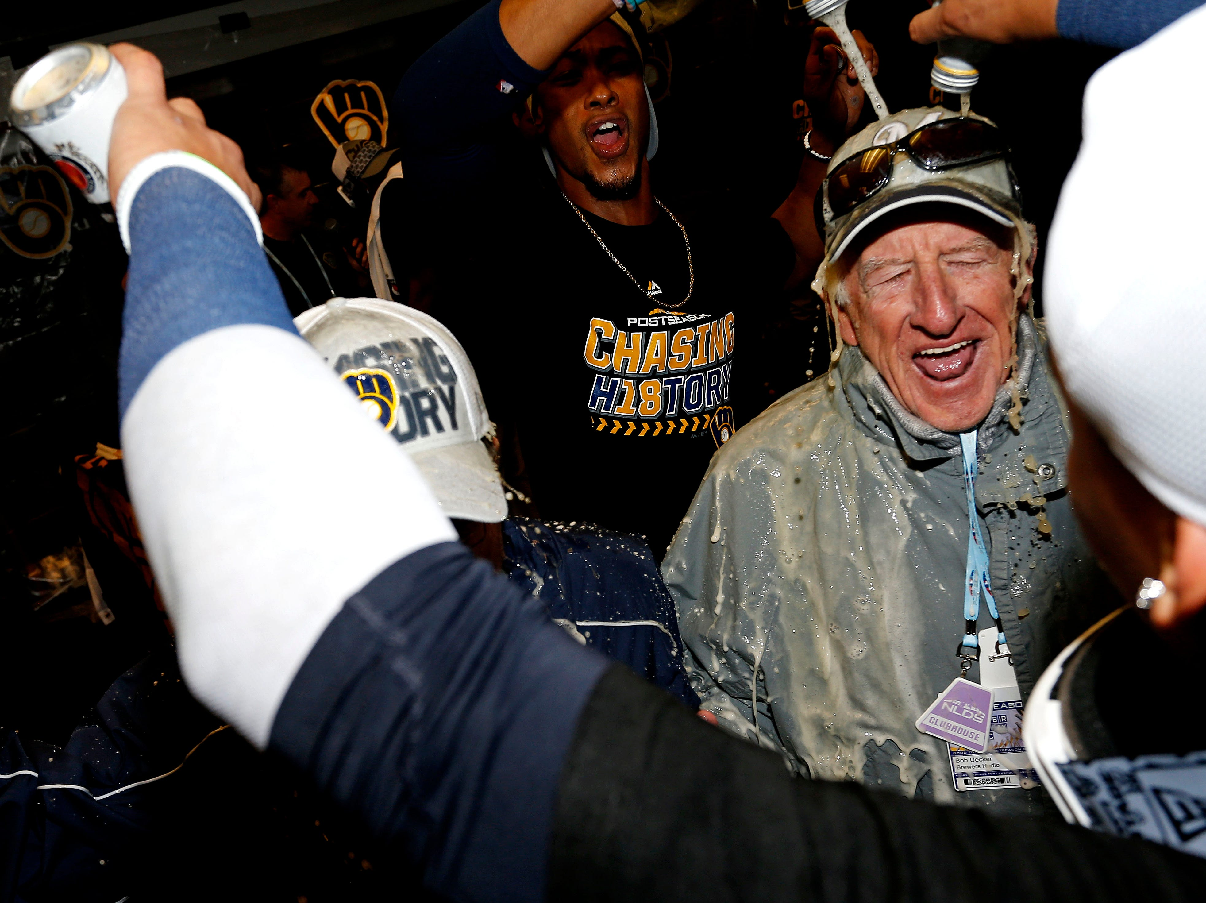 NLDS Game 3: Brewers players celebrate in the clubhouse with broadcaster Bob Uecker.
