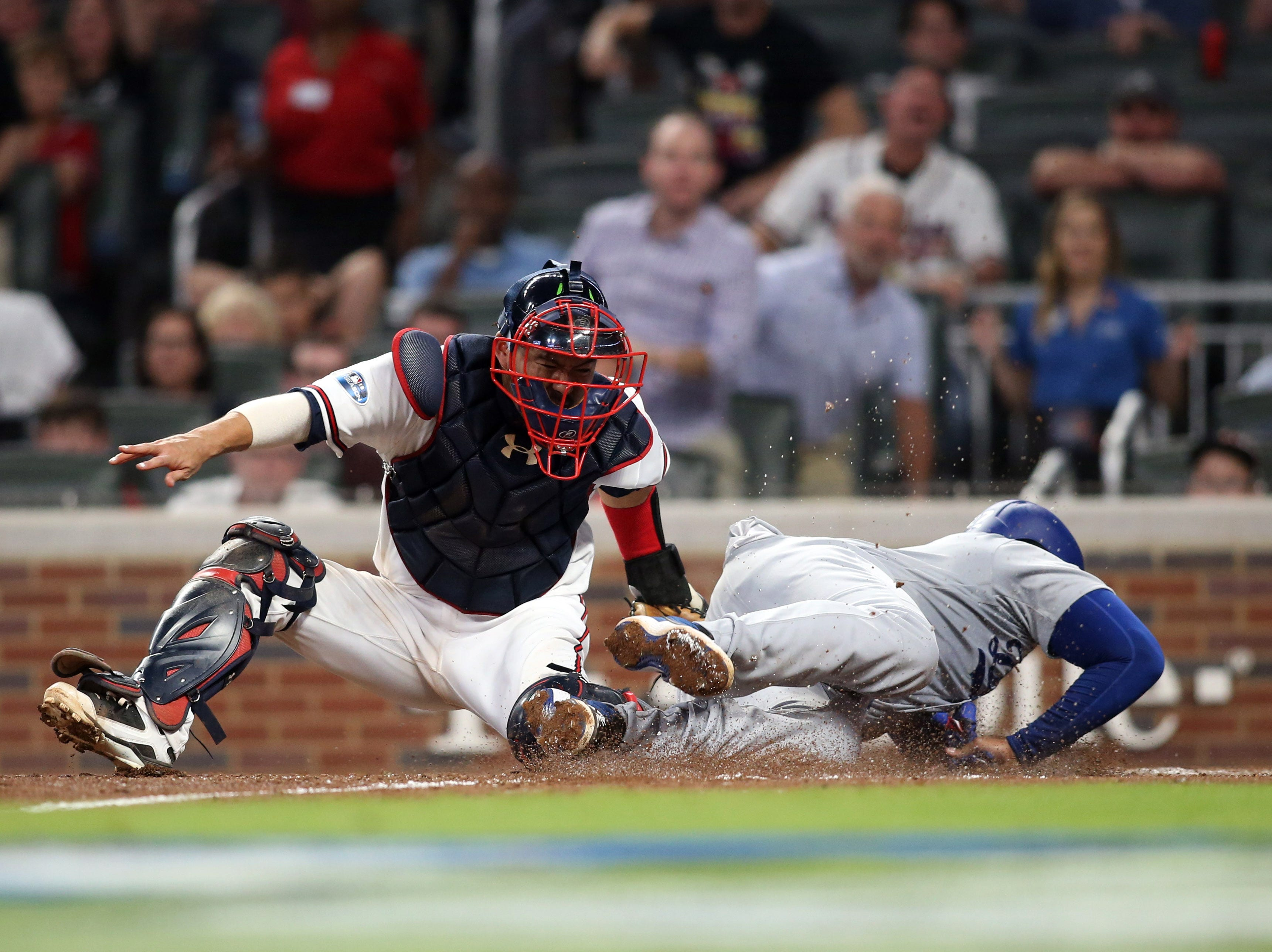 NLDS Game 3: Braves catcher Kurt Suzuki tags out Matt Kemp at the plate in the sixth inning.
