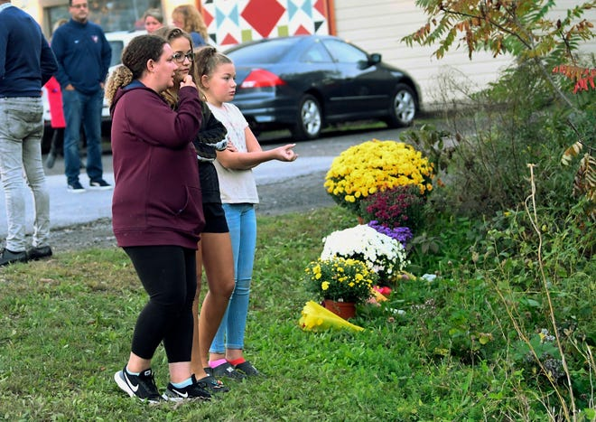 Friends of victims that died in the limousine crash comfort each other after placing flowers at the intersection in Schoharie, N.Y. on Oct. 7, 2018.