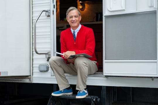 "Tom Hanks puts on the red cardigan as Mr. Rogers in ""A Beautiful Day in the Neighborhood."""