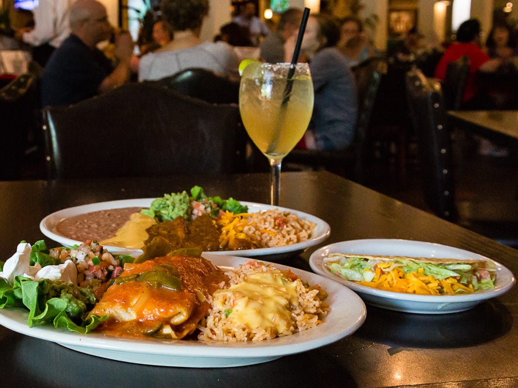 """Here are four classic Tex-Mex items on the menu at El Fenix (clockwise from front): chimichanga plate, """"El Fenix Dinner"""" combo plate that includes one cheese enchilada with chili con carne, one picadillo beef taco, two tamales with chili con carne and guacamole."""