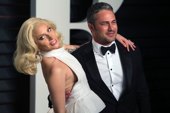 Taylor Kinney and his former fiancée, Lady Gaga, embrace at the 2016 Vanity Fair Oscar Party.