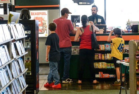 James Werner, manager at the Family Video store in Anderson, checks out movies for the Davin family. Werner said he's worked at the store long enough to see kids who used to come in with their parents now have their own accounts.