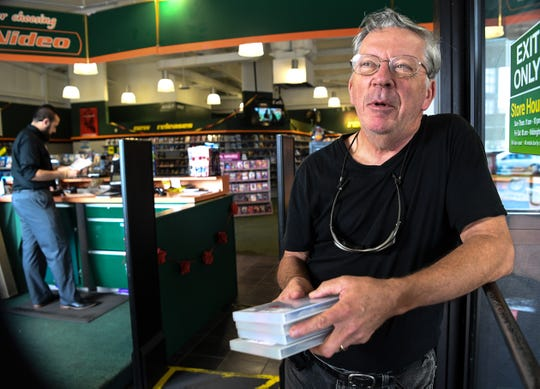 Reggie Titmas of Anderson checks out a stack of movies near manager James Werner, left, at the Family Video store in Anderson.