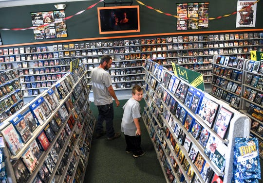 Zenas Todd, left, and his son Oliver Todd of Starr browse the shelves for movies. Todd said looking at the cases is part of the fun of renting a movie and brings back childhood memories.